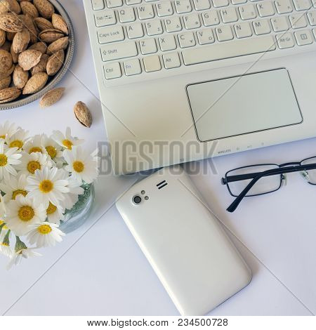 Workspace With Computer At Home , A Desk With Flowers And White Smartphone. Near Almonds And Spectac