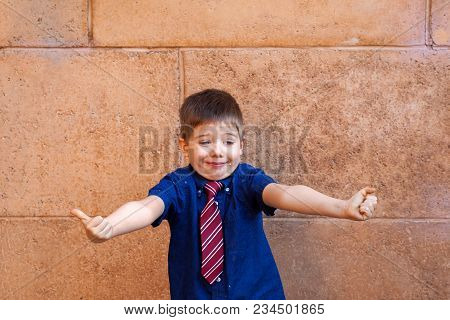 A Well Dressed, Little Boy Wearing A Tie, Stands In Front Of A Large Block Wall With His Arms Out An