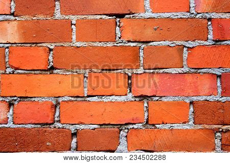 Red briks wall. New brick wall texture. The crumbling wall of bricks. Wall texture background. The plaster on the wall. Uneven wall surface. The paint on the wall. Plastered walls. Abstract background. Painted brick wall