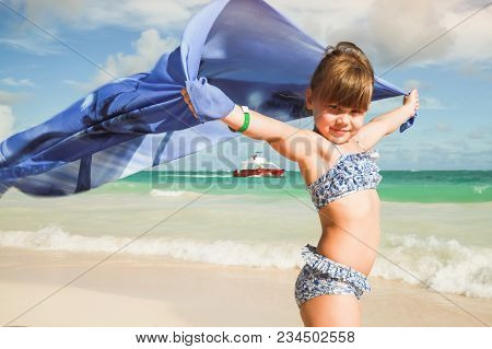 Little Blond Caucasian Girl With Blue Shawl On Sandy Beach In Sunny Windy Day