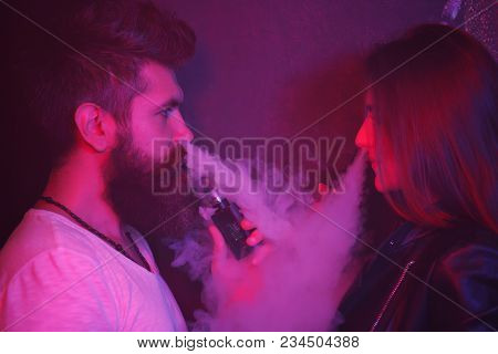 Man And Woman Standing Smoking E-cigarettes With Lowe Angle View Off The Middle-aged Man Exhaling Sm