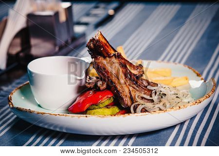 Plate With Rack Of Lamb, Grilled Vegetables And French Fries. Clouse Up. Plate On The Table With A T
