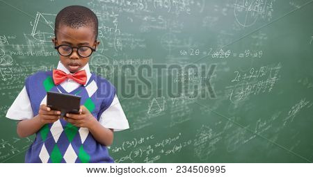 Boy in vest and bowtie with calculator against green chalkboard with math doodles