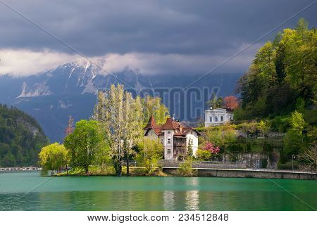 Scenic View Of Lake Bled - Popular Tourist Attraction In Julian Alps - With Quay In Sunlit And Mount
