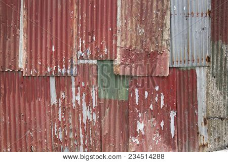 Close-up Detail Of Old Rusty Red Corrugated Metal Panels Assembled Roughly Into A Wall