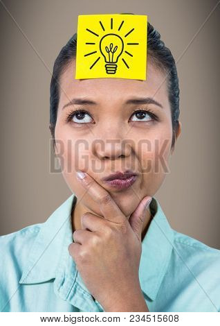 Woman thinking with yellow sticky note on head showing grey lightbulb graphic against brown backgrou