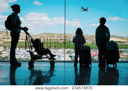 Mother With Kids And Luggage Looking At Planes In Airport, Travel Concept