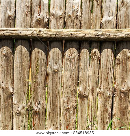 Old Weathered Log Wall. Wooden Fence From Old Vertical Logs. Square. Close-up.