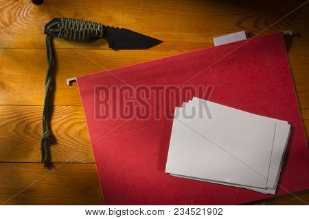 Army Knife And Photos With A Folder On A Wooden Table