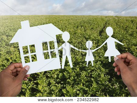Cut outs house and family in hands over landscape