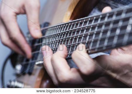 Closeup Photo Of Bass Guitar Player Hands, Soft Selective Focus, Live Music Theme,