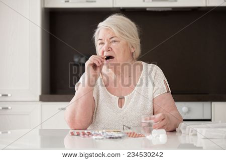 Grandmother Sits At The Table. A Pensioner Takes Pills.