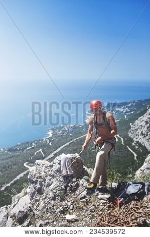 Man Rock Climber Stands On The Top Of The Cliff And Belays A Partner