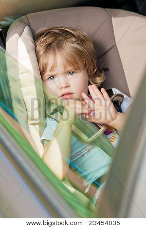 little girl sitting in car safety seat.shot made through window pane poster