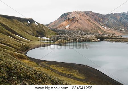 Beautiful Icelandic Landscape With Rocky Hills, Green Vegetation And Calm Water