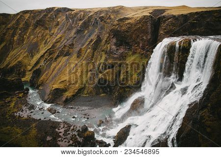 Scenic Icelandic Landscape With Majestic Fagrifoss Waterfall And Rocks With Green Vegetation