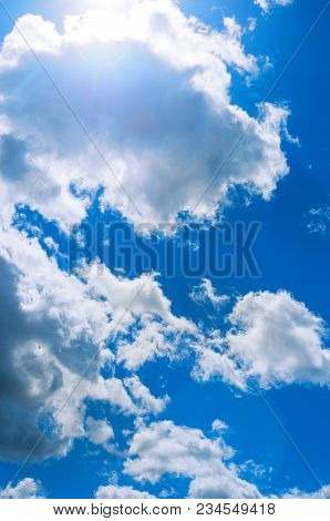 Sky Landscape Of Blue Cloudy Sky With Sunlight Beams. Blue Sky Background With White Dramatic Clouds