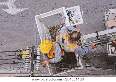 Two Electricians Worker Working In The Cradle Of The Manipulator Safety Belt Forklift Man-lift Safet
