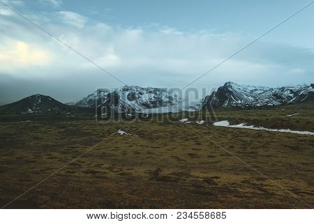 Beautiful Snow-covered Mountains And Green Vegetation On Meadow In Iceland