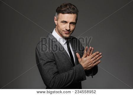 Photo of unshaved successful man 30s wearing office suit and black tie smiling on camera holding hands together isolated over gray background poster