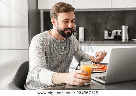 Smiling adult man 30s wearing casual clothing eating scrambled eggs for breakfast and drinking juice at home while using laptop