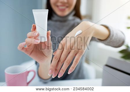 Close Up Of Girl's Hands. She Is Holding A Small Tube With Hand Cream In One Hand And Showing Her Ot