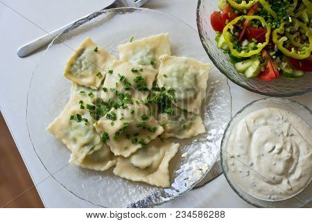 Freshly Cooked Ravioli On A Plate Sprinkled With Green Onions. Next To The Bowls With Cream Sauce An