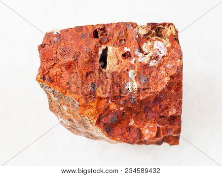 Macro Shooting Of Natural Mineral Rock Specimen - Rough Red Bauxite Stone On White Marble Background
