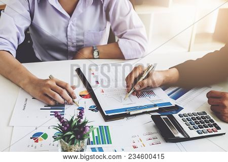 Business Financial Concept. Busines Sman And Partner Pointing Graph Paper Are Meeting To Plan Sales