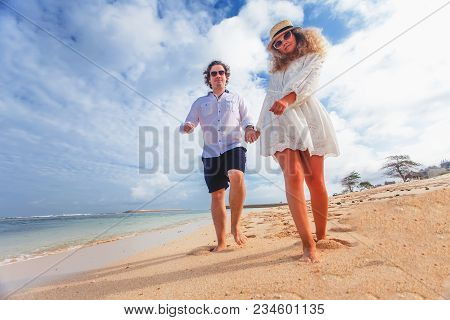 Wedding Couple Just Married Holds Hands And Walking At The Beach, Bali. Successful Married Couple. B