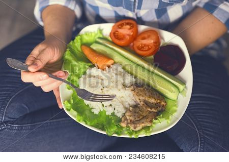 A Girl Holds A Plate With Vegetables And Chicken Meat With Spices. Healthy Eating Concept. Girl In J