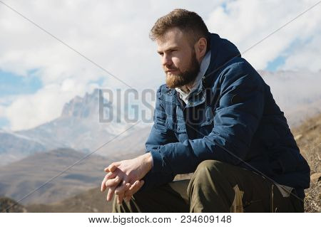A Portrait Of A Stylish Smirk Bearded Hipster Sitting On A Rock Against The Backdrop Of Epic Rocks A