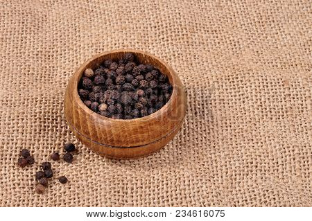 Pepper Not Ground In A Wooden Bowl On A Ragged Background