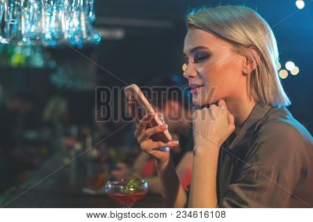 Side View Pensive Female Typing In Mobile While Tasting Alcohol Liquid. Technology And Rest In Club
