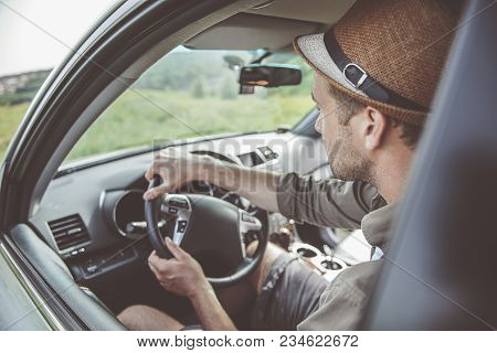 Side View Of Serious Young Man Is Driving His Car With Concentration. He Is Traveling Across Country