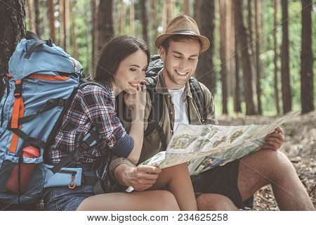 Glad Loving Couple Is Sitting And Reading A Map In Forest. Woman Is Hugging Man With Smile