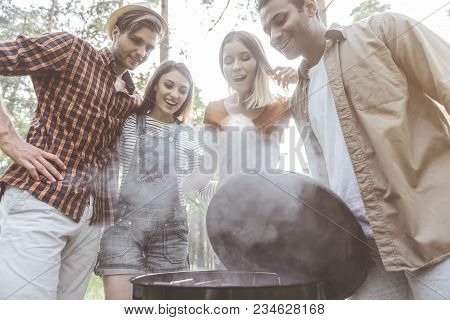 So Delicious. Low Angle Of Four People Standing Over Open Grill And Looking At Food With Eager