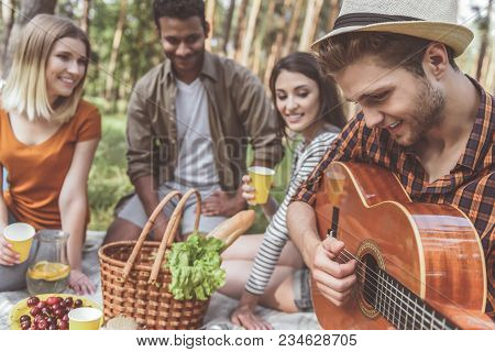 Focus On Handsome Guy In Hat Playing The Guitar While Sitting With Friends On Picnic. They Are Drink