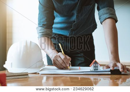 Engineer Man Working With Drawings Inspection In Workplace In Office. Engineering Construction Conce