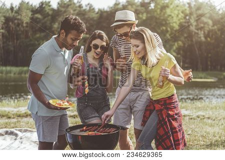 Delighted Men And Women Standing Near Barbecue And Looking At Appetizers With Eager. They Holding Bo