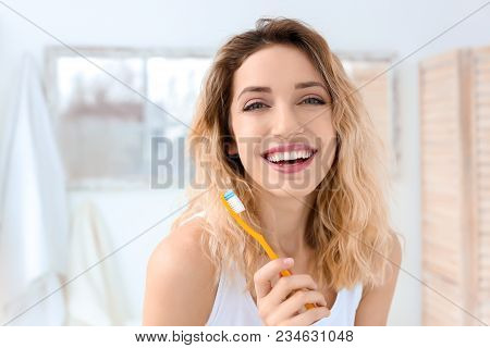Young Woman Brushing Her Teeth In Bathroom