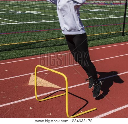 A High School Track And Field Athlete Is Inches Off Of The Ground As She Jumps Over A Yellow 2 Foot