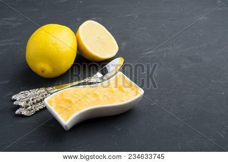 Lemon Curd In White Jar On Dark Grey Background With Copy Space