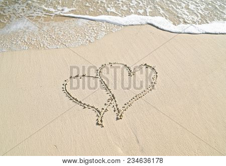 Pair Of Hearts In Beach Sand With Frothy Ocean Surf