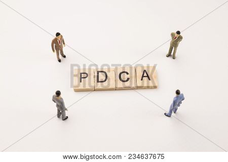Miniature Figures Businessman : Meeting On Pdca Letters By Wooden Block Word On White Paper Backgrou