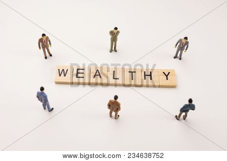 Miniature Figures Businessman : Meeting On Wealthy Letters By Wooden Block Word On White Paper Backg