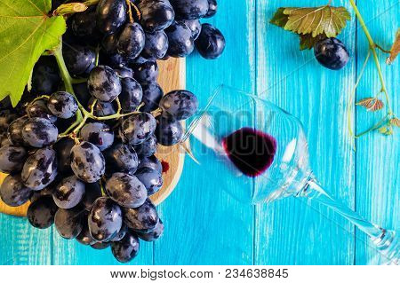 Grapes And Wine Glass On A Blue Wooden Table, Top View. Branch Of Fresh Ripe Red Grapes. Beautiful B