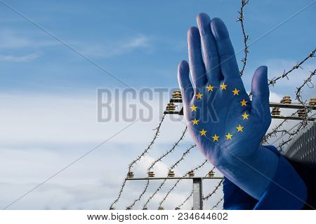 Hand With European Flag Stops Immigration Of Refugees, Blurred Border Fence In The Background, Blue