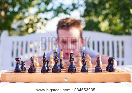 Boy Thinking Over Chess Game. Black Chess Pieces. The Beginning Of The Chess Game. Selective Focus