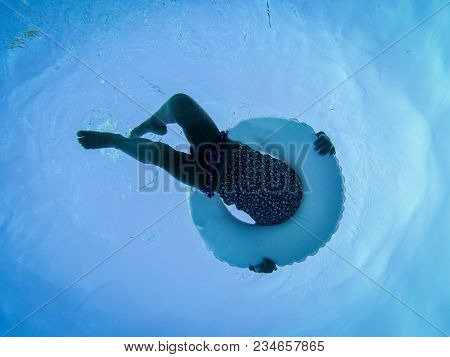 Underwater Photo Of Girl Swimming In Pool With Circular Floating Buoy, Unrecognizable